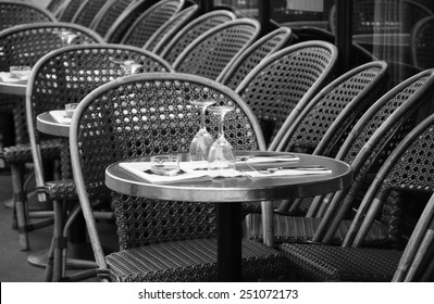 Parisian cafe terrace. Selective focus on the glasses. Aged photo. Black and white.