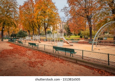 Parisian deserted playground in Autumn with green benches and autumn leaves everywhere