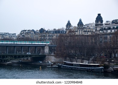 Parisian metro on Bir-Hakeim bridge with typical houses in the background on cloudy day - Paris, France