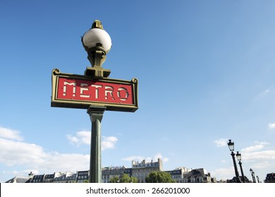 Parisian metro sign with a lamppost against blue sky