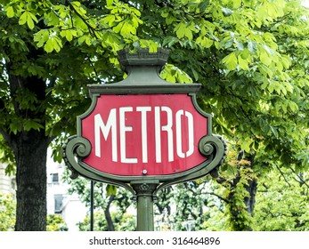 Parisian metro sign with a lamppost against old vintage wall