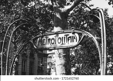 Parisian metro sign on empty street in sunny day. Plane trees and typical house building at background. Paris, France. Vintage background. Old times, nostalgia concept. Black white historic photo.