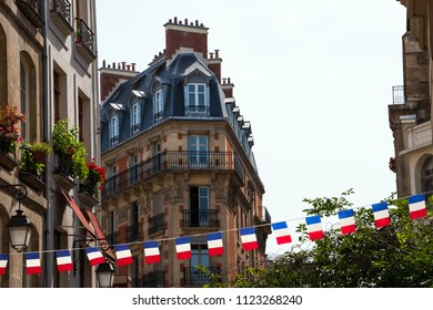 Parisian street decorated with French flags garland. Paris, France. National holiday celebration concept.