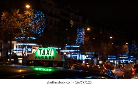 A Parisian taxi for hire at Avenue des Champs-Elysees decorated with Christmas illumination.
