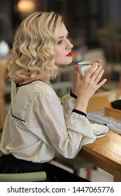 A  parisian woman in a cafe drinking coffee