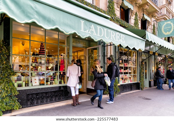 PARIS-JAN 5, 2014: Shoppers at the famous Laduree bakery and tea room in Paris. Laduree was founded in 1862 and is a luxury brand known for its macaroon cookies in many flavors and colors
