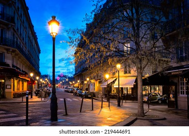 PARIS-JAN 5,2014:Paris street at night in one of the oldest neighborhoods, with cobblestone streets and charming buildings, cafes, restaurants and shops lit by street lamps. Ile Saint-Louis