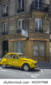 PARIS-JULY 22,2012: Street scene, typical french car, yellow citroen 2CV in front of a bakery.