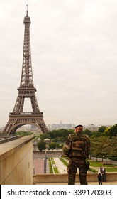 PARIS-MAY 24, 2015: Behind French soldier in uniform standing at palace Trocadero looking at the Eiffel Tower in clouded day.