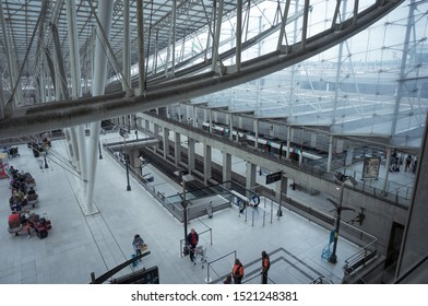 Paris-Roissy-Charles de Gaulle Airport, France - July 2019 - Waiting hall of the railway station above the station platform and under a massive metal frame, passengers with luggage sitting on benches