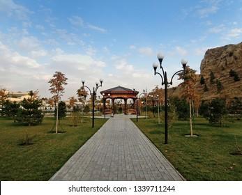 Park alley with pavilions near Mausoleum of Hodja or Hooja Doniyor (biblical Daniel). Green zone located near by river Siab in Samarkand, Uzbekistan. Rocks on background are Afrasiyab