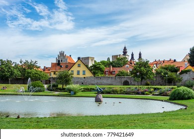 Park Almedalen in Visby, the main city on island Gotland, Sweden. The best-preserved historical medieval city in Scandinavia. Beautiful view with color old buildings, lake, resting or relaxing people.