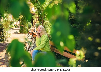 I am in park already waiting for you. Blonde enjoy relax in park or garden. Active girl with bicycle. Woman with bicycle in blooming park garden. Active leisure and lifestyle. Girl calling friend.