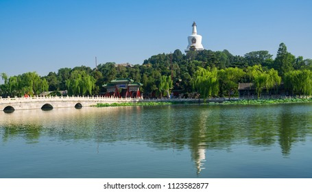 Park Beihai in Beijing , China, with white pagoda and blue sky.  This is a public park in the center of downtown Beijing.  It used to be an imperial garden for many dynasties.