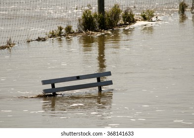 A park bench flooded by a river overflowing its banks.