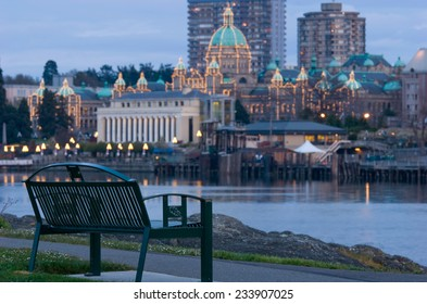 Park bench in foreground looks over inner harbour and Parliament Buildings near dusk, Victoria, BC, Canada