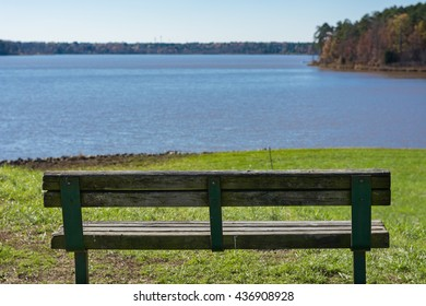 Park bench on hill in front of lake