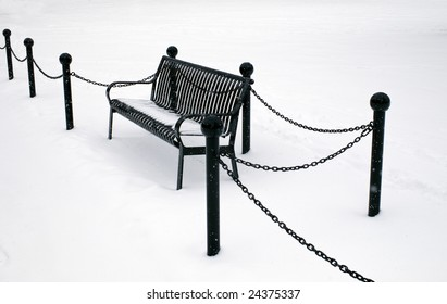A park bench with snow all around.