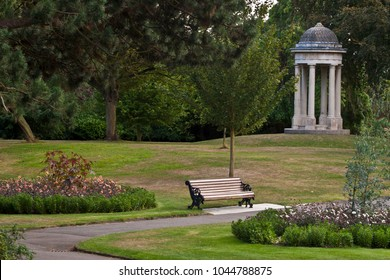 Park in Chelmsford, Essex, United Kingdom. A footpath, a bench, flowers and trees.