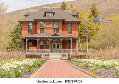 Park City Public Library and former Miners Hospital with spring daffodils. Park City, Utah, USA.