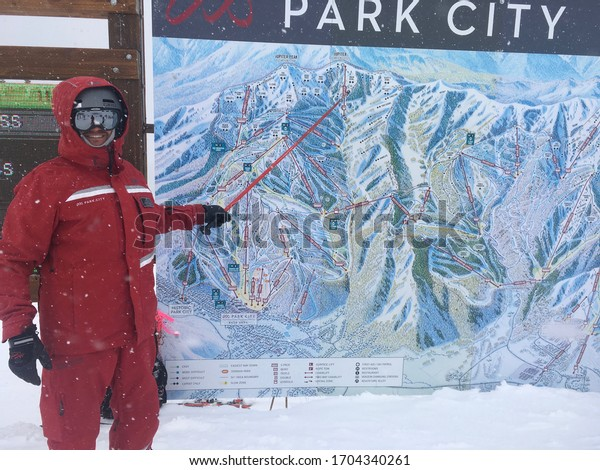 Park City, Utah, February 2018. A smiling Park City Mountain Resort host employee standing near a ski resort map with it snowing.  Vail Resorts owns Park City Mountain.