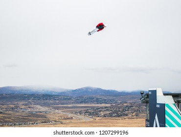 Park City, Utah/USA - Oct. 6, 2018: male freestyle skier flying into the air from a practice ski ramp at Utah Olympic Park with the Wasatch mountains in the distance