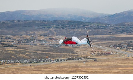 Park City, Utah/USA - Oct. 6, 2018: male freestyle skier in profile flying through the air during training at Utah Olympic Park with the Wasatch mountains in the distance