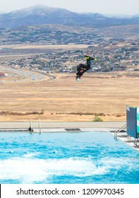 Park City, Utah/USA - Oct. 6, 2018: female freestyle skier flying through the air before landing in a practice pool at Utah Olympic Park with Wasatch Mountains in the distance