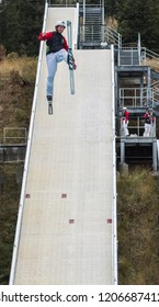 Park City, Utah/USA - Oct. 6,2018: male freestyle skier flying down a practice ramp at Utah Olympic Park while other skiers watch