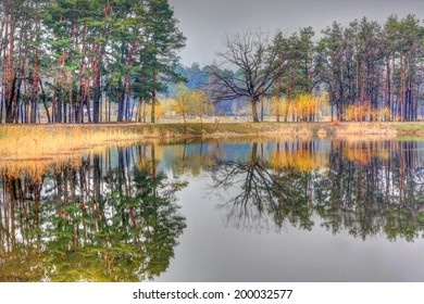 park in early spring with trees reflecting in the lake