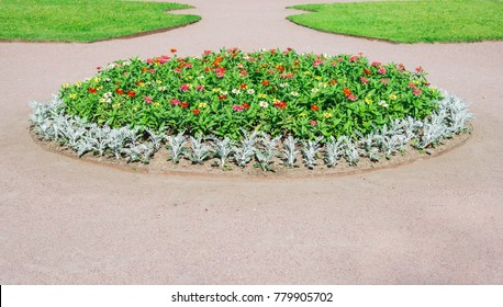 Park with flowerbed and green lawns landscape design. Topiary, green decor in the park. Flowerbed. Flowers of different color