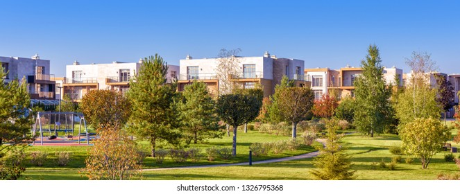 Park with gardens in modern town,  landscape of green public place. Panoramic view of landscaped area near residential houses. Scenic panorama of nice trees in summer, concept of city life and nature