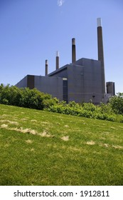 Park greenspace with coal-powered electric generating station with four smoke stacks in background.