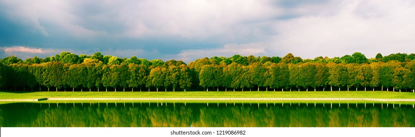 Park landscape involve alley of trimmed trees, embankment and pond in orthogonal form (axial dominant). Perfect nature in Renaissance view as art of gardening, regular garden, landscape architecture