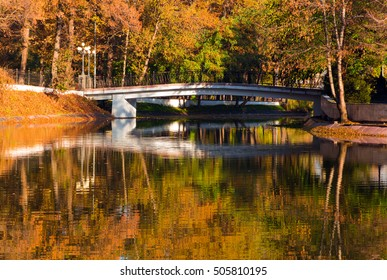 Park in the morning. Reflections of a bridge and trees in the lake.