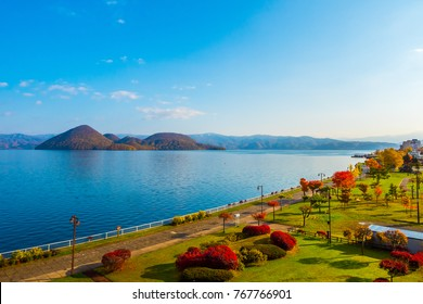 Park near Lake Toya in Toyako town, Hokkaido, Japan.  Lake Toya in beautiful morning with cloudy blue sky and mountain background.
