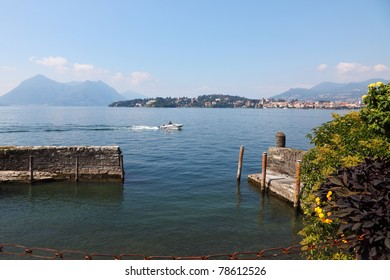 Park on the waterfront of the island of Isola Bella. Fishing boat on lake