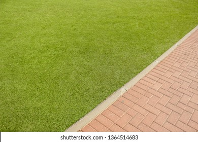park outdoor aerial exterior wallpaper pattern with diagonal board between green grass and brown brick paved road background textured surfaces with empty copy space for your text