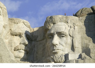 A park ranger and photographer standing above Abraham Lincoln at Mount Rushmore National Memorial, South Dakota