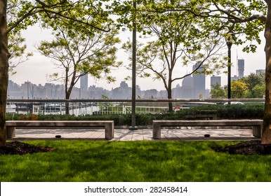 Park sitting area landscape with urban skyline background. Metropolis skyline behind a park area. Trees and park benches framing a spring morning. Skyscrapers as background for outdoor sitting area.