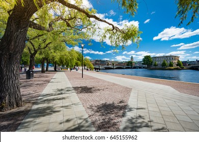 Park in Stockholm, Sweden, Scandinavia, Europe. Trees and walking lanes with old town, blue sky with clouds (gamla stan) in background.
