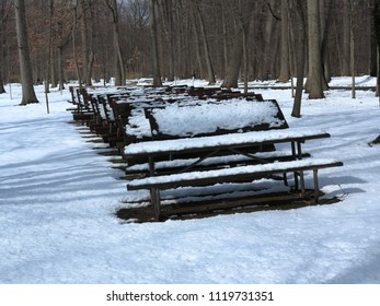 Park in Winter - Benches stacked with park closed for the season with snow cover in winter.