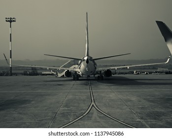 A parked aircraft in an airport isolated unique black and white photo