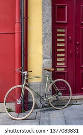 Parked bicycle next to a red door in Oporto, Portugal