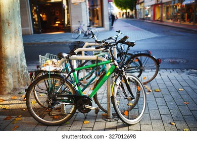 Parked Bicycles On Sidewalk. Bike Parking On The Street.