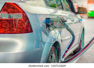 Parked car refueling pump, with computer screen with graph, Concept of energy business and stock market fluctuations.