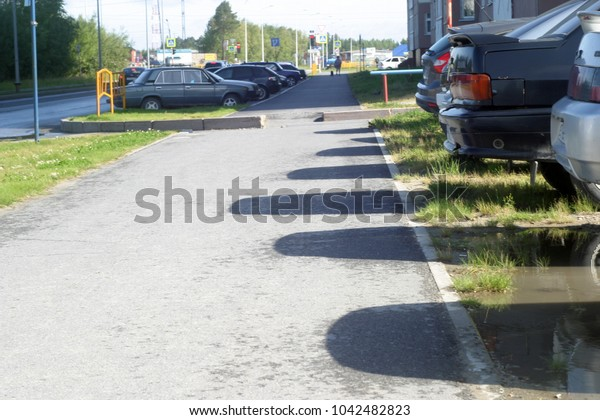Parked cars cast shadows on the road. Summer background