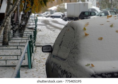 Parked cars covered with beautiful white snow. The first snow in the fall. Winter holiday background