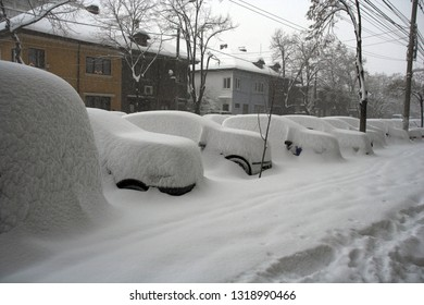 Parked cars covered by a thick layer of snow