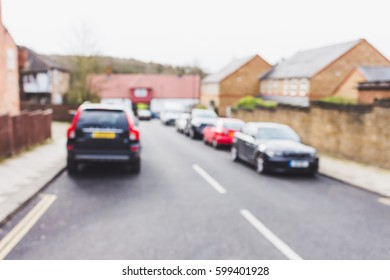 Parked cars on the side of the road, suburb, London, UK, blurred background.